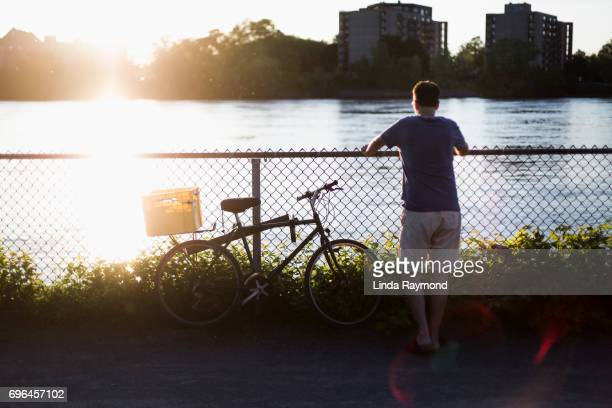 A man looking away by a river with a bike beside him at sunset