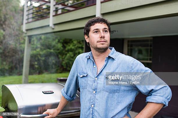 Man Looking Away In Yard Against House