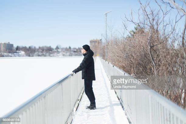 A man looking away on a bridge during winter