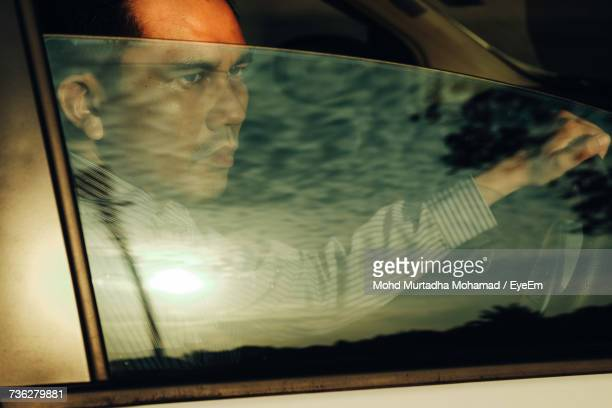 Man Looking Away While Sitting In Car