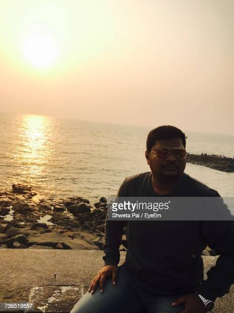 Man Looking Away While Sitting On Retaining Wall Against Sea During Sunset