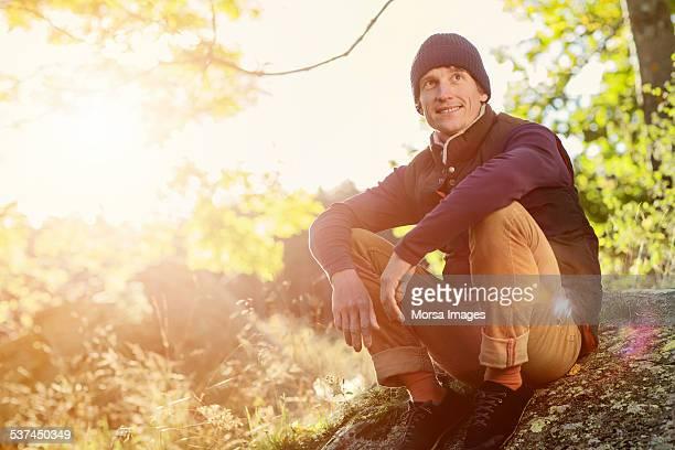 Man looking away while sitting on rock