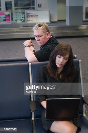 Man looking behind shoulder at woman's laptop screen