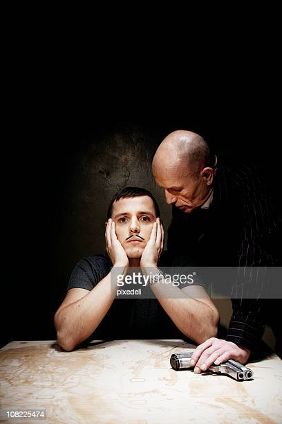 Man Looking Bored While Being Interrogated by Male Holding Gun