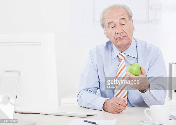 Man looking doubtfully at an apple