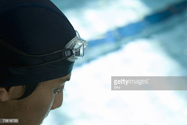 Man looking down swimming pool, high angle view, close up, differential focus