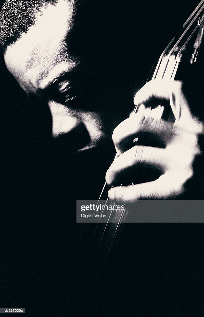 Man looking down while playing double bass