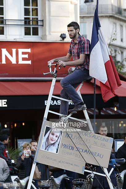 A man looking for his cousin of whom he awaits news since the attacks at the Bataclan music hall on November 13 rides on a bike at the Place de la...