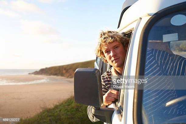 Man looking from camper van window beside beach.