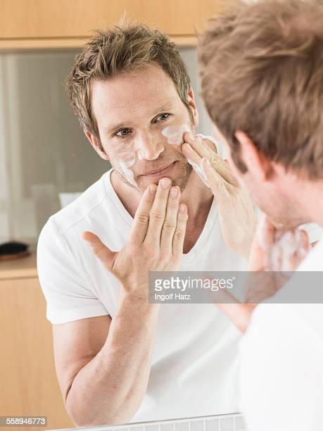 Man looking in bathroom mirror applying face cream