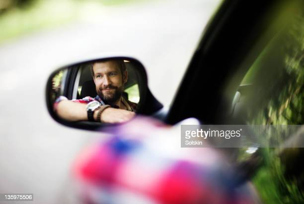 man looking in car mirror