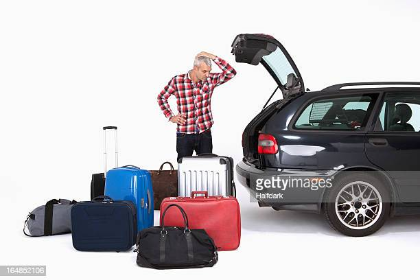 A man looking in disbelief at the amount of luggage he has to fit in his car