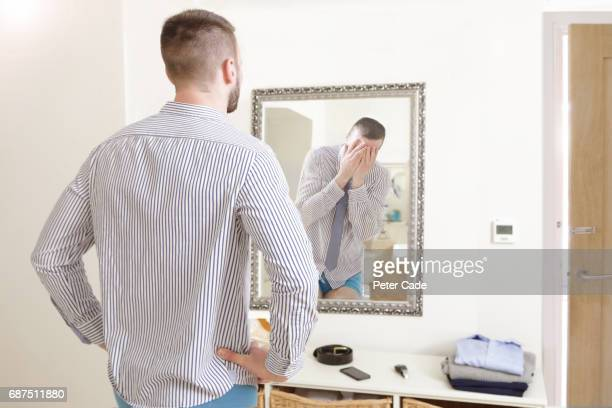 Man looking in mirror at distressed reflection