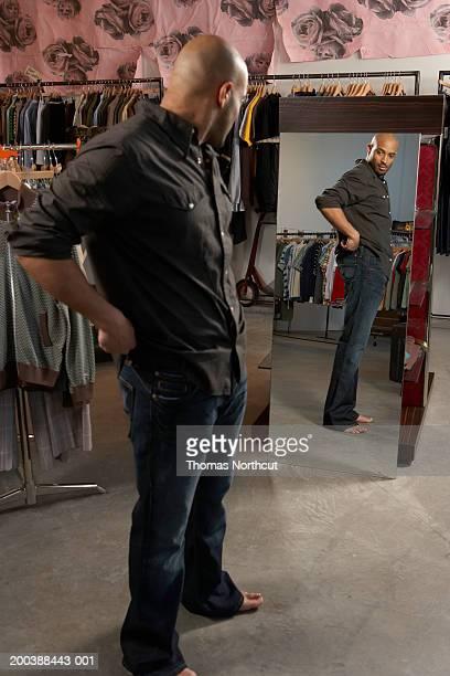 Man looking in mirror in retail store, side view (focus on mirror)