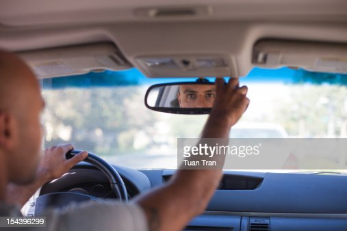 man looking in rear view mirror of car : Stock Photo
