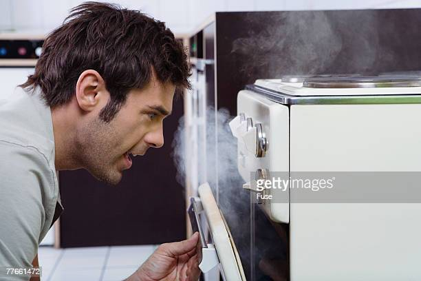 Man Looking in Smoking Oven