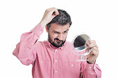 Horrified young man looking in the mirror at the first grey hair on his scalp