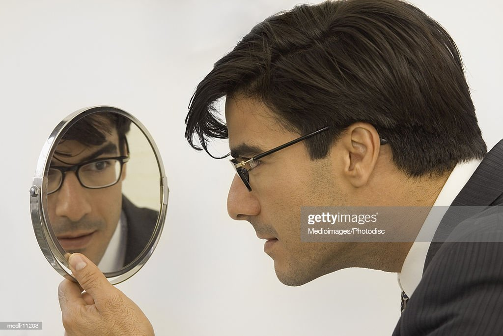 A man looking into a mirror : Stock Photo