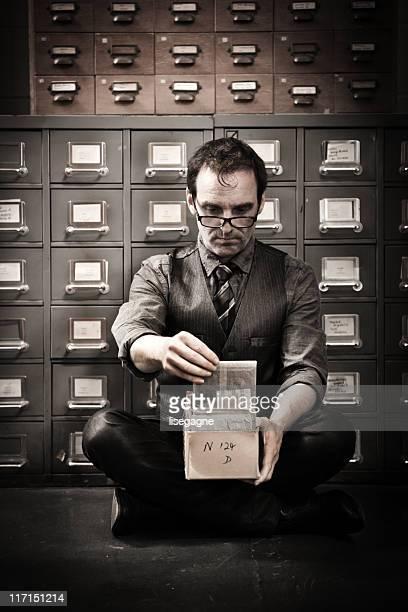 Homme à la recherche dans la case pour les photographies d'archives