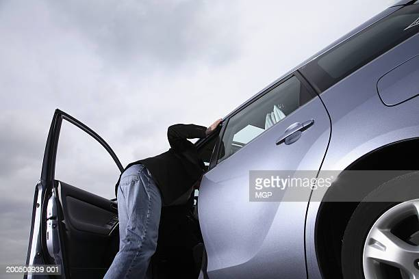 Man looking into car, side view