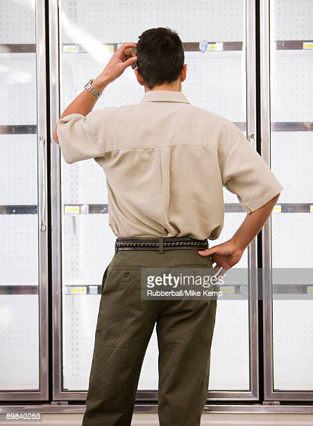 man looking into empty refrigerators at market