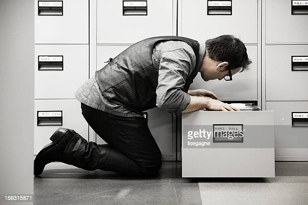 Man looking into filing cabinet