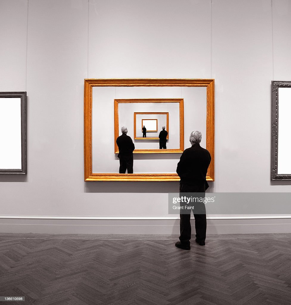 Man looking into framed image. : Stock Photo