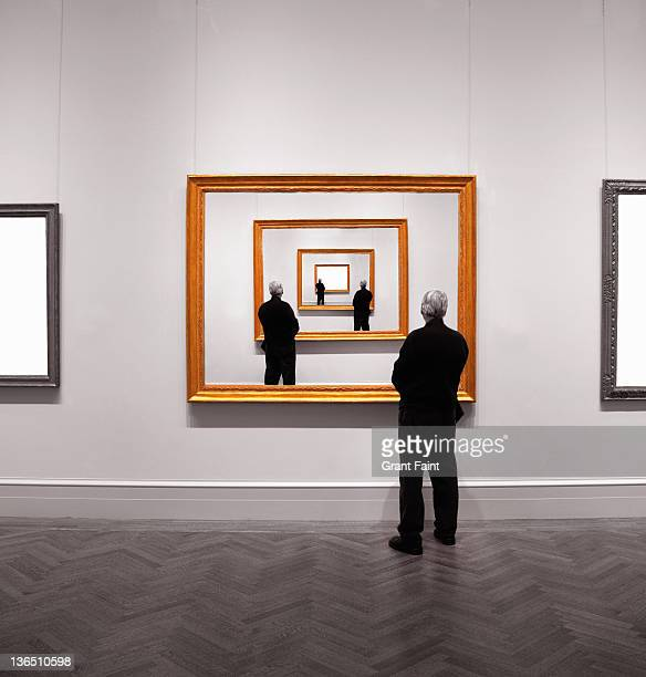 Man looking into framed image.