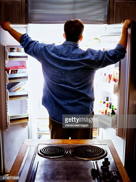 Man looking into refrigerator for food.
