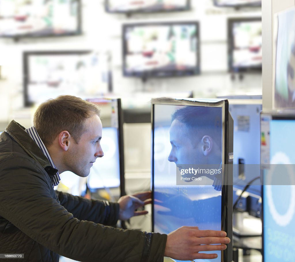 Man looking into television screen in shop : Stock Photo