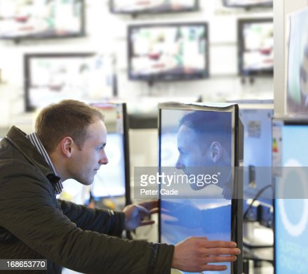 Man looking into television screen in shop