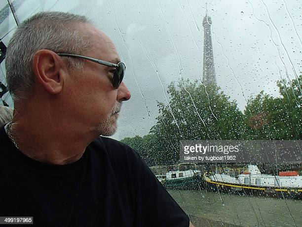 Man looking out a window from river boat
