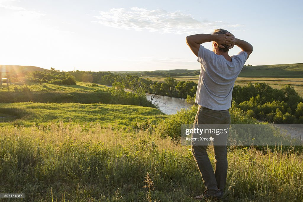 Man looking out across prairie landscape