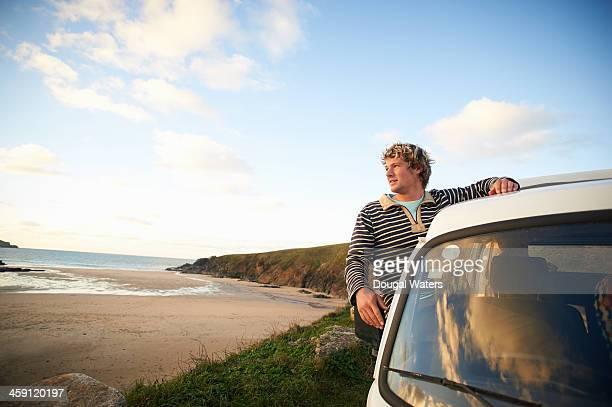 Man looking out along coastline from camper van.