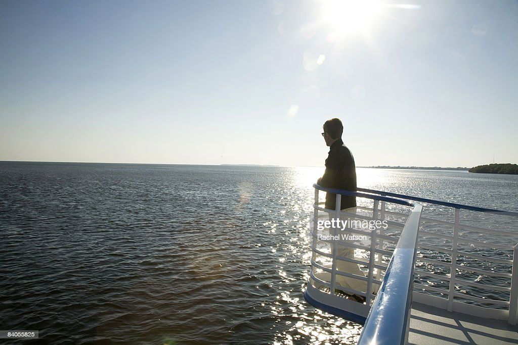 Man looking out from boat, side view : Stock Photo