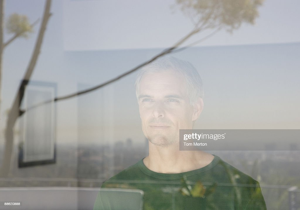 Man looking out living room window : Stock Photo