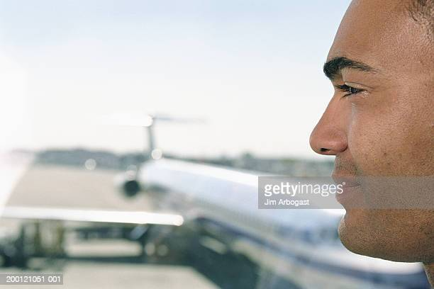 Man looking out of airport window, profile, close-up