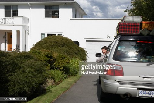 Man looking out of window of car on front drive, smiling