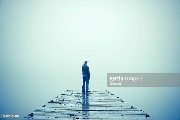 Man Looking Out Through Fog and Standing on Dock