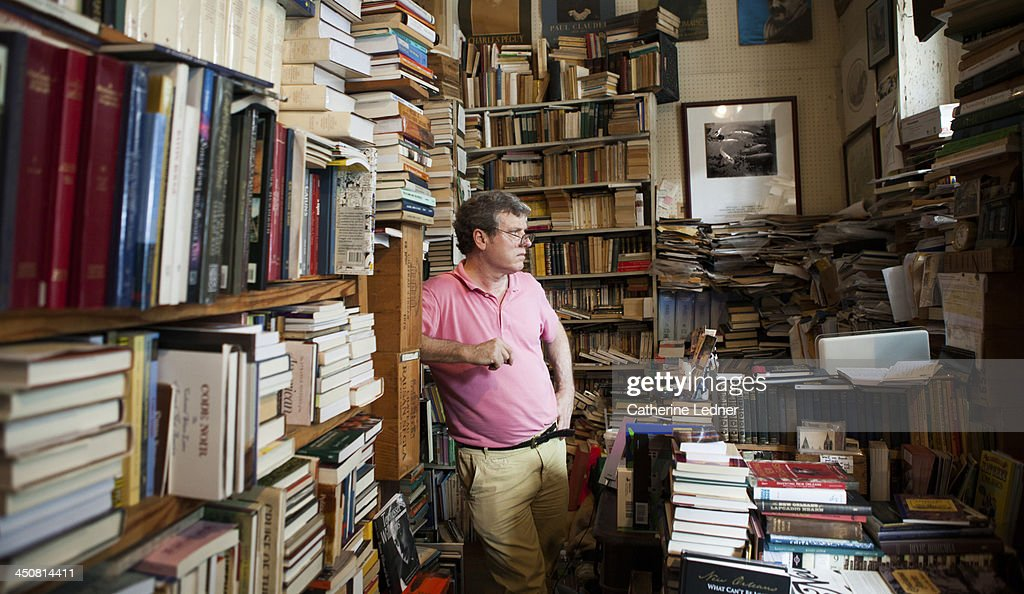Man looking out window in small bookstore : Stock Photo