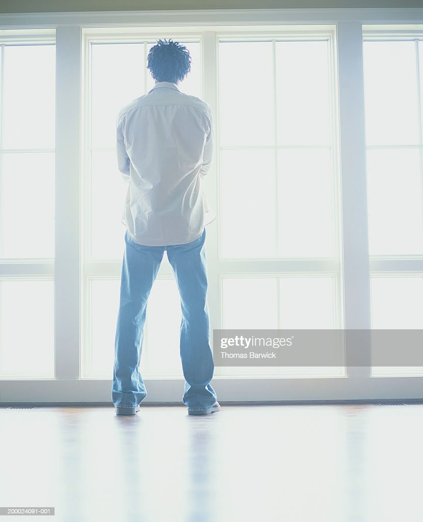 Man looking out window, rear view, low angle view