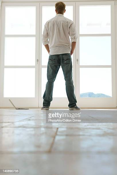 Man looking out window, rear view