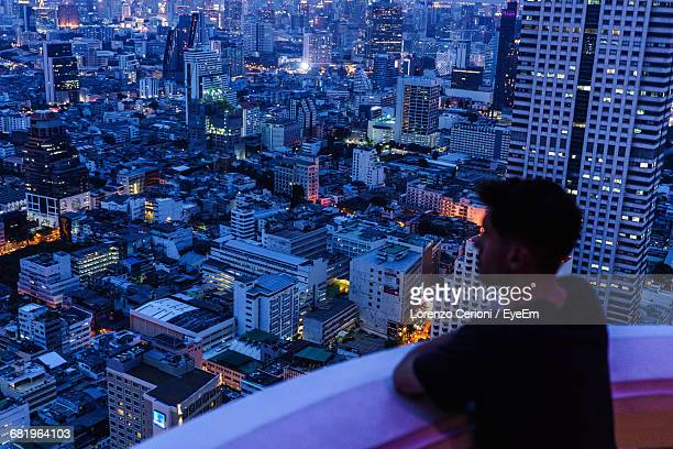 Man Looking Over A City At Night
