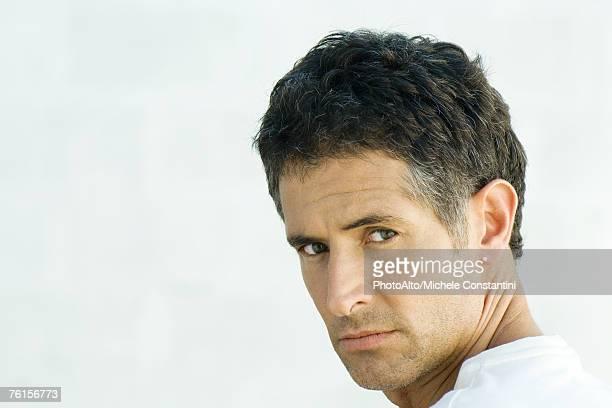 'Man, looking over shoulder at camera, portrait'