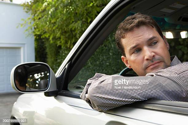 Man looking over shoulder out of window of car on driveway, close-up