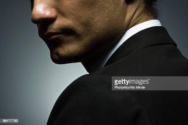 Man looking over shoulder with suspicion