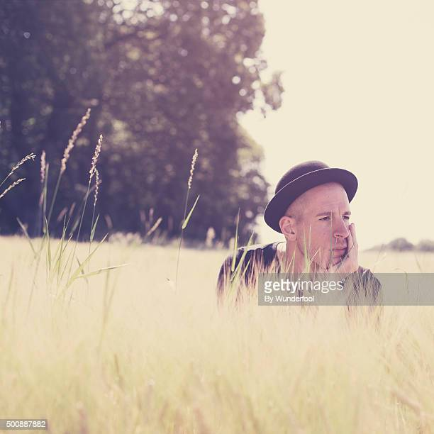 Man looking over tall grass in a bowler hat