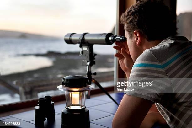 Man looking through a telescope