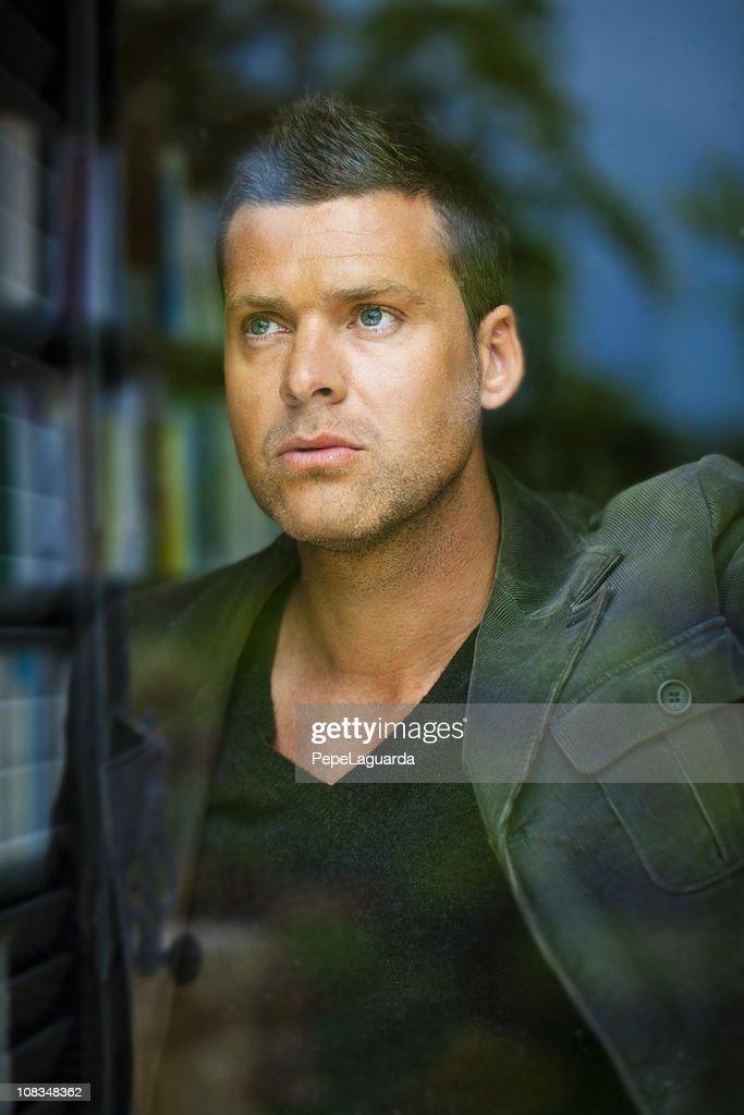 Man looking through an office window : Stock Photo