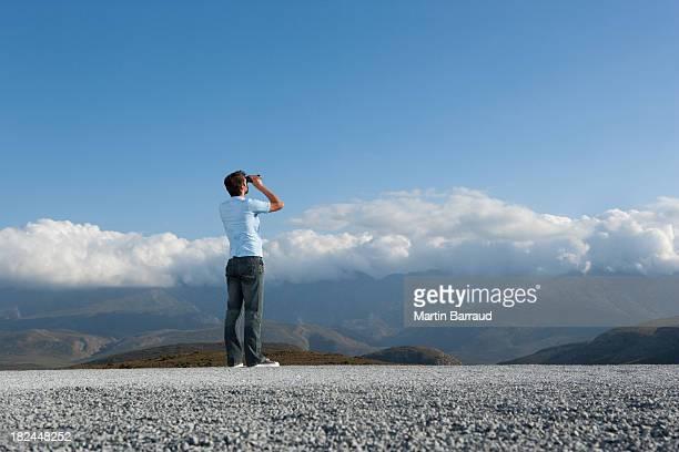 Man looking through binocular at outdoors